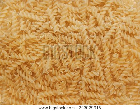 Macaroni in the form of bows are laid out on the table in the form of a background of a product from durum wheat for cooking food for cooking