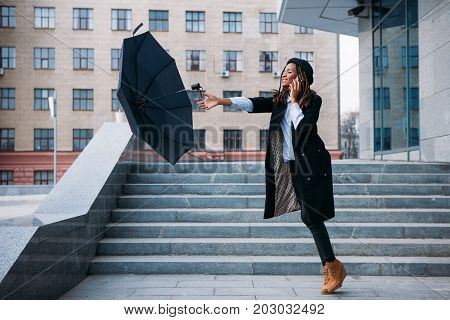 Stormy weather. Black girl catch flying umbrella while speaking on mobile phone on street, airiness concept