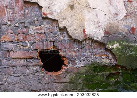 Texture of old brick wall with broken plaster and hole.