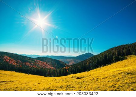 Orange mountains and sun in blue sky
