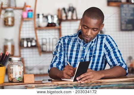 Focused young African entrepreneur standing at the counter of his trendy coffee shop writing down notes in a book