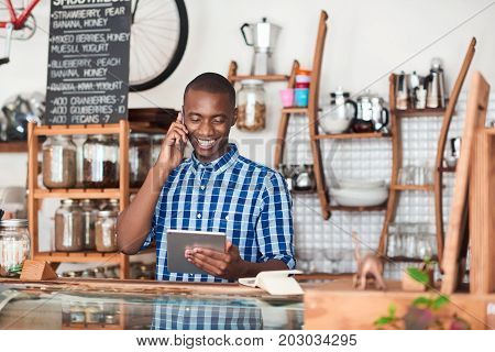 Smiling young African entrepreneur standing at the counter of his cafe talking on a cellphone and using a digital tablet
