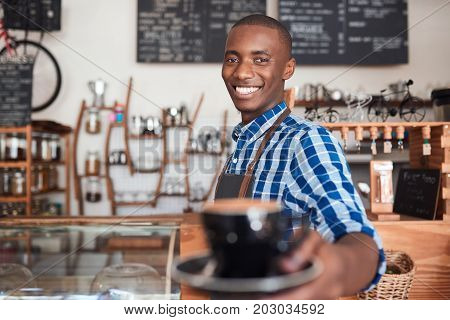 Portrait of a smiling African barista standing at the counter of a trendy cafe offering up a fresh cup of cappuccino
