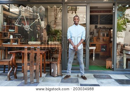 Portrait of a smiling young African entrepreneur standing welcomingly at the entrance of his trendy cafe