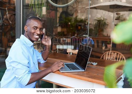 Portrait of a smiling young African man sitting at a counter of a sidewalk cafe talking on his cellphone and working on a laptop