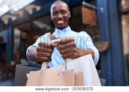 Portrait of a stylish young African man smiling and holding up shopping bags while out shopping in the city