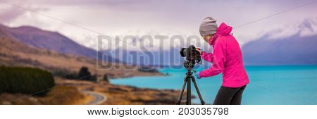 Woman photographer taking picture of travel landscape panoramic banner. New Zealand nature photography with slr camera on tripod at sunset with autumn background at Peter's lookout