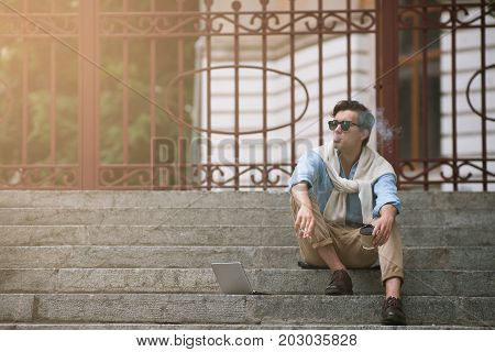 Young smoking man on coffee break on urban background. Bad habits. Unhealthy lifestyle, modern student life, hipster concept