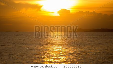 Sunset with sunlight or sunrays or sunbeams over sea or ocean with orange or golden light tone.