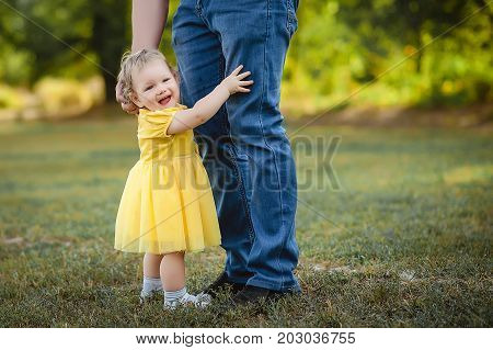A little girl in a yellow dress hugs her father's pants.