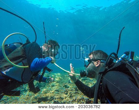 Scuba Diver Out Of Air - Buddy Breathing. A helpful dive buddy shares his air.