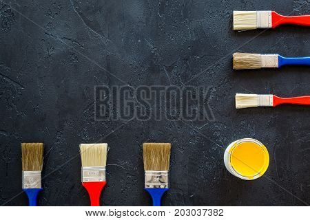 house-painter desk with set of building implements, pain, brushes on dark desk background top view mock up