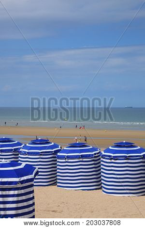 beach in summer with tents sun and blue sky France Normandy city of Cabourg