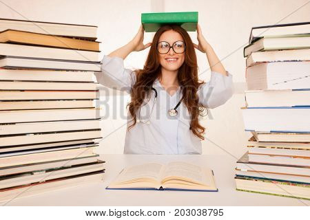 attractive beautiful young medicine student with book on her head