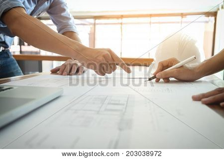 Image of engineer or architectural project Close up of Architects engineer's hands drawing plan on BluePrint and discussing to partner with Engineering tools on workplace Construction concept.