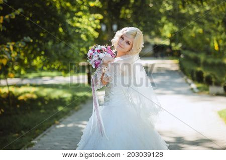 An innocent young bride boasts her veil.