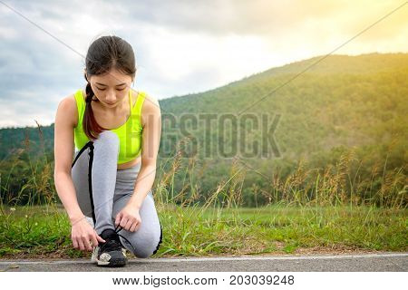 Shot of young woman runner tightening running shoe laces getting ready for jogging exercise outdoors. Female jogger lacing her sneakers standing on road path before morning run.