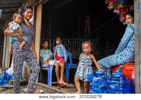 SIHANOUKVILLE CAMBODIA - 7/20/2015: A family at their local store in a rural fishing village.