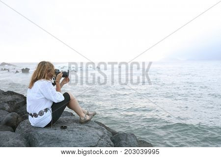 Young girl photographer on the shore of Pico Island, Azores, Portugal, Europe