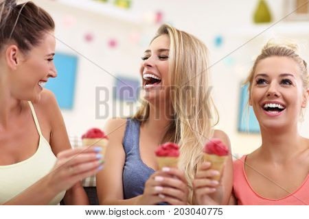 Three beautiful young women eating ice-cream at home