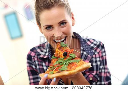 Beautiful young woman eating pizza at home