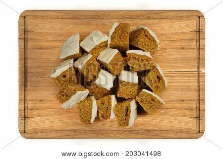 Top view glazed  mini pieces of carrot cake on wooden plate isolated over white background