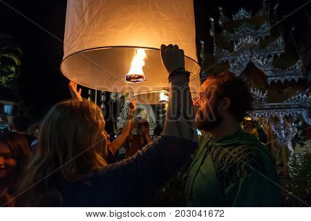 CHIANG MAI THAILAND - 12/30/2015: Tourists release floating lanterns at a Buddhist temple on New Year's Eve in Chiang Mai Thailand.
