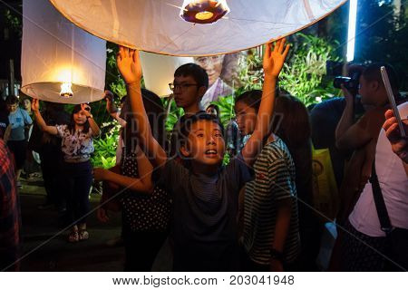 CHIANG MAI THAILAND - 12/30/2015: A young boy releases a floating lantern at a temple on New Year's Eve in Chiang Mai Thailand.