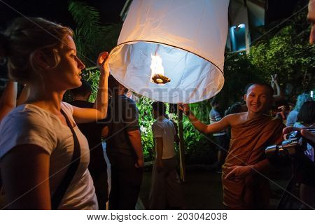CHIANG MAI THAILAND - 12/30/2015: A Buddhist monk and a tourist release a floating lantern at a temple on New Year's Eve in Chiang Mai Thailand.