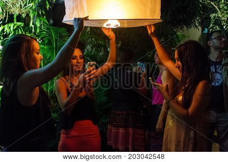 CHIANG MAI THAILAND - 12/30/2015: Young female tourists release a floating lantern at a Buddhist temple on New Year's Eve in Chiang Mai Thailand.