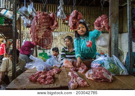 PHNOM PENH CAMBODIA - AUGUST 11 2015: A meat vendor waits for customers in the Russian market in Phnom Penh.