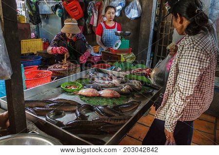 PHNOM PENH CAMBODIA - AUGUST 11 2015: Customers browse the fish selection in the Russian market in Phnom Penh.