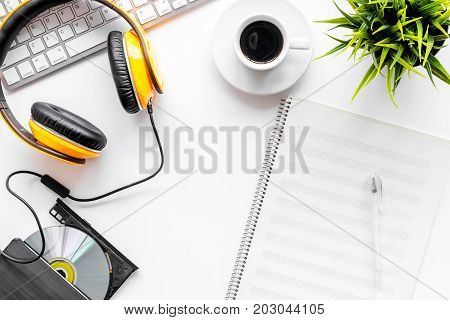 songwriter or dj work place with music notes, headphones and blank paper on white desk background top view mock up