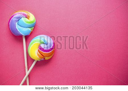 rainbow lollipop on pink color background. sweet candy