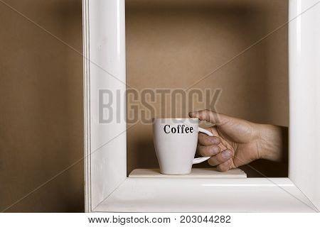 Human hand in painting frame holding a mug with coffee cropped studio shot