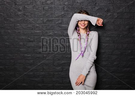 Young woman in gray dress and braids smiling and posing coquettishly on black background.