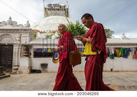 KATHMANDU NEPAL - 9/23/2015: Tibetan monks walk around the Boudhanath Stupa in Kathmandu Nepal.