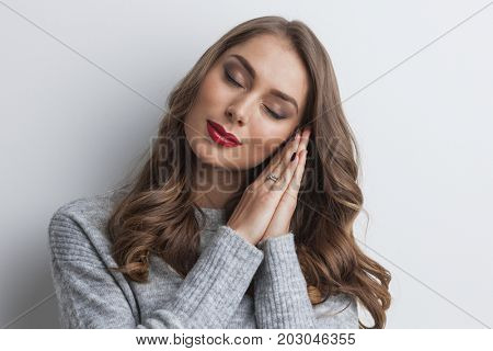 Beautiful young woman holding her hands on her chick and dreaming with eyes closed
