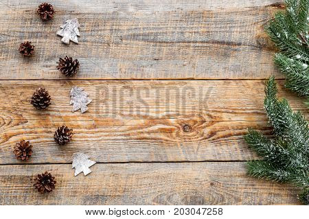 pine cones to decorate christmas tree for new year celebration with fur tree branches on wooden table background top veiw mockup