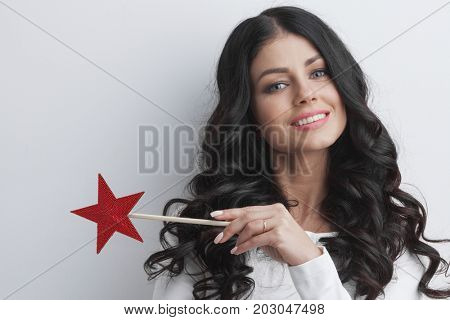 Gorgeous woman magician with star shaped magic wand