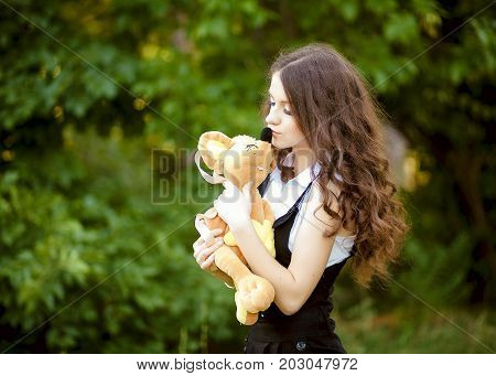 An innocent young brown-haired woman in a forest with a plush toy.