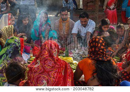 KATHMANDU NEPAL - 9/26/2015: Hindu men and women in colorful sari sit in a circle at Durbar Square in Kathmandu Nepal.