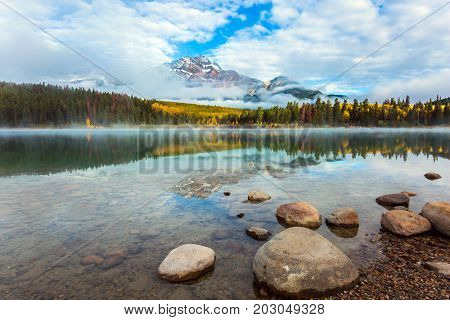 Indian Summer in Canada. Patricia Lake among the firs and pines. Lush clouds are reflected in the smooth water. The concept of extreme and ecotourism