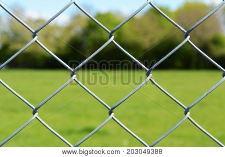 Metal chain link fencing in selective focus. Beyond the secure fence lies an empty green field lined by trees.