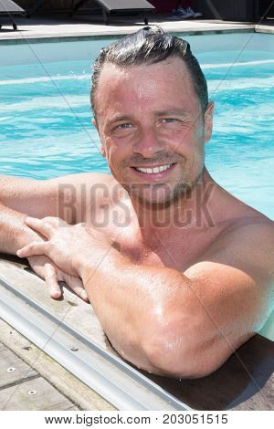 Handsome And Happy Mid Aged Man Relaxing Resting On His Hands At The Side Of A Sun Bathed Swimming P