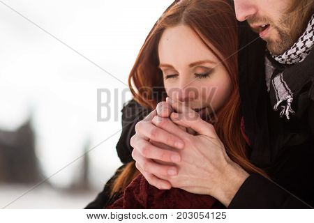 Young winter couple in warm clothes - warmth of love.