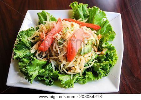 Papaya Salad, Shredded green papaya, tomatoes, green beans, crushed peanut and lime dressing