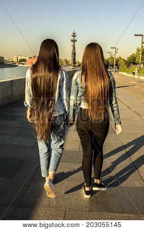 Two long-haired girls walking along the embankment holding hands. The concept of friendship love and non-traditional relations.