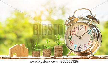 wooden house model and step of coins stacks with tree growing on top and clock alarm nature background money saving and investment or family planning concept over sun flare silhouette tone.