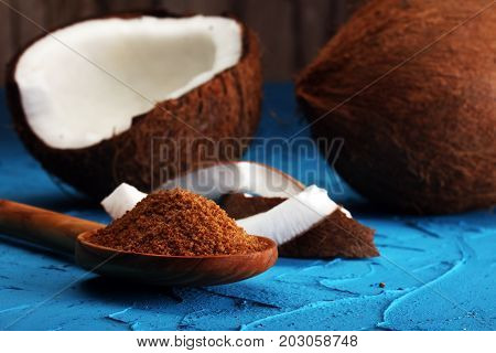 Scoop Of Brown Sugar With Coconut On Blue Background